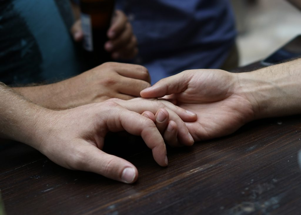 People hold hands at the Ember restaurant as reports come in about the shooting at the Pulse nightclub in Orlando. (Mandel Ngan / Getty Images All rights reserved.)