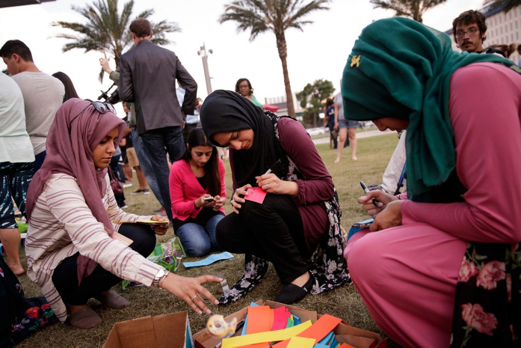 ORLANDO, FL - JUNE 14: Saamiya Pirbhai (L) and Atiya Karim (C), from Husseini Islamic Center in Sanford, Florida, write notes for a prayer chain at a makeshift memorial at the Dr. Phillips Center for Performing Arts, June 14, 2016 in Orlando, Florida. The shooting at Pulse Nightclub, which killed 49 people and injured 53, is the worst mass-shooting event in American history. (Photo by Drew Angerer/Getty Images)